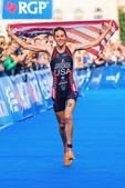Estocolmo -, 24 de agosto: el ganador gwen jorgensen corriendo hacia la línea de meta con la bandera de estados unidos en el evento mujeres itu world triathlon serie 24 de agosto de 2013 en estocolmo, suecia — Foto de Stock