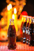 Glass bottles of Coca Cola displayed in a Christmas setting — Stock Photo