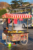 Man with a colorful cart selling fresh roasted sweet corn and roasted chestnuts — Stock Photo