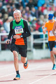 Older man running the final stretch at Stockholm Stadion — Stock Photo