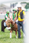 Pony racer warming up with her trainer and horse before the star — Stock Photo