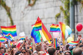 Happy crowd waving rainbow flags — Stockfoto