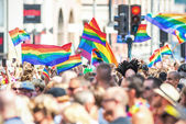 Happy people waving rainbow flags at the Stockholm Pride Parade — Stock Photo