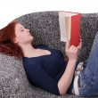 Stock Photo: Woman relaxing with book on couch