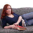 Royalty-Free Stock Photo: Woman relaxing with book on couch