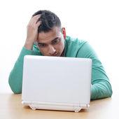Young man staring at netbook — Stock Photo