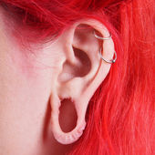 Stretched ear lobe piercing — Stock Photo