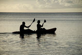 Silhouetted kayakers on the ocean — 图库照片