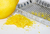 Grated lemon zest with the fruit and grater — Stock Photo