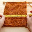 Two hands measuring knitting in inches — Stock Photo #23704529