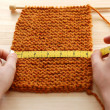 Stock Photo: Two hands measuring knitting in inches