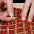 Stock Photo: Closeup of two hands pinning red plaid fabric