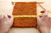 Two hands measuring knitting in inches — Stock Photo