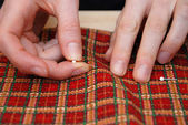 Closeup of two hands pinning red plaid fabric — Stock Photo