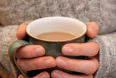 Two hands keeping warm, holding a hot cup of tea or coffee — Stock Photo