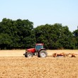 Stock Photo: Tractor and harrow cultivating soil