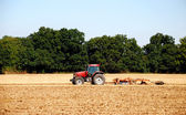 Tractor and harrow cultivating the soil — Foto Stock