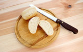 Fresh rolls, whole and halved, with bread knife — Stock Photo