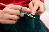 Closeup of woman knitting with teal wool — Stock Photo