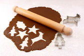Rolling pin and festive cookie cutters with gingerbread dough — Stock Photo