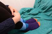 Woman hugging her legs, wearing warm socks — Stock Photo