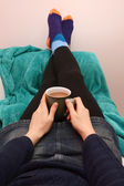 Woman holding a hot drink, relaxing with her feet up — Stock Photo
