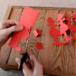 Cutting a chain of red paper dolls with scissors — Stock Photo #40160637