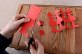 Cutting a chain of red paper dolls with scissors — Stock Photo