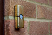 Brass-coloured doorbell on a brick wall — Stock Photo