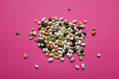 Mixed dried beans and peas on a pink background — Stock Photo