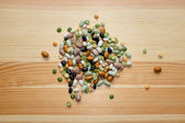 Mixed dried beans and peas on a wooden background — Stock Photo