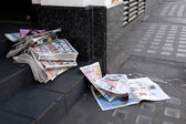 Tabloid newspapers abandoned in a shop doorway — Stock Photo