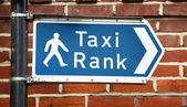 Signpost points to a taxi rank — Stock Photo