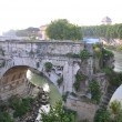 Stock Photo: The ancient dilapidated bridge with an arch