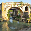 The ancient dilapidated bridge with an arch — Stock Photo