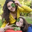 Two beautiful teenager having fun playing in the garden with green leafs on their eyes — Stock Photo