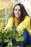 Beautiful yellow shirt girl teenager relaxing happy in the garden holding green leafs — Stock Photo