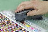Spektrofotometr ověřit barevné skvrny na testovací arch, press shop předtiskových oddělení — Stock fotografie