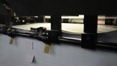 Gros plan d'une machine offset en imprimerie. le département de stockage des feuilles imprimées de matière à la fin de la machine — Vidéo