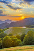 Sunset in the mountains landscape with a shepard house — Stock Photo