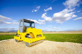 Yellow road-roller on repairing of the road — Stockfoto