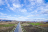 Strait road through the fields — Стоковое фото