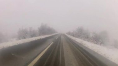 "Driving around ""S"" curve on snowy country road — Wideo stockowe"