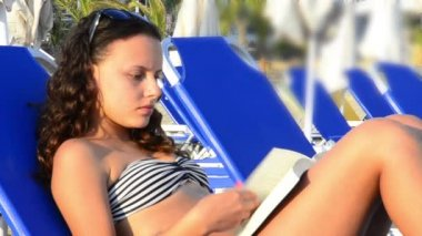 Girl Sunbathing & reading book at the beach — Stock Video