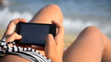 Woman using smartphone on beach — Stock Video