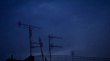 Thunderbolts and lightnings in a night over building top TV antennas — Stock Video