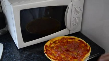 Microwave oven pizza preparation home kitchen — Stock Video