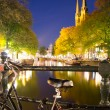 Bike and canal in amsterdam at night - Stock Photo