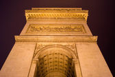 Side view of the Arc de Triomphe biulding in Paris, France at ni — Stock Photo