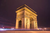 Side vie of Arc de Triomphe in Paris at night — Stock Photo